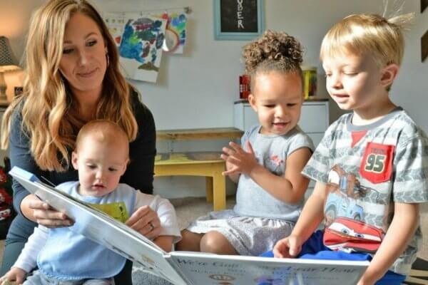 Childcare professional reading a book to three kids